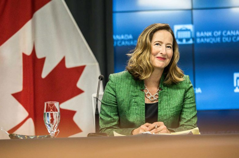 Carolyn A. Wilkins smiling while sitting at a table in the Bank of Canada's press conference room.