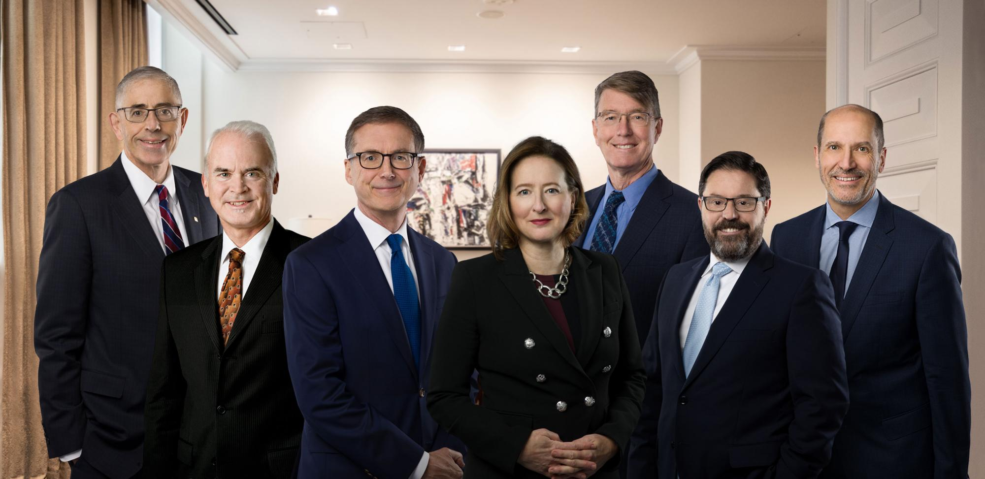 The seven members of the Bank's Executive Council formally standing together outside a meeting room at head office.