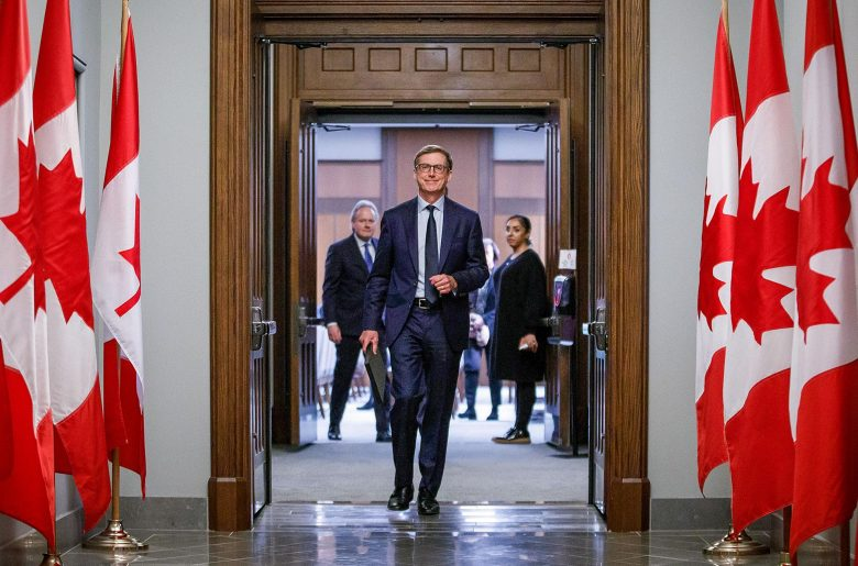 Tiff Macklem walking confidently into the House of Commons. Canadian flags line the hallway.